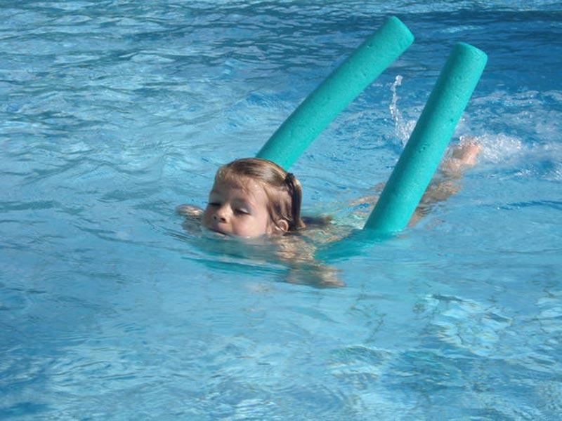 Carouge Natation - Camp école de natation - Jeune fille nageant avec un flotteur